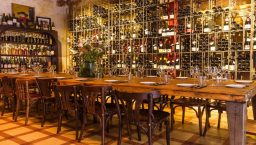 Bar à vin Brutal: longue table et mur de bouteilles